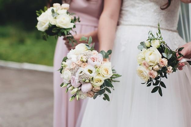 Braut im weißen kleid, das hochzeitsstrauß mit brautjungfern hält