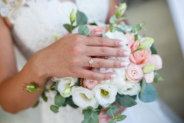 Braut im weißen kleid hält einen blumenstrauß