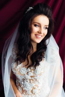 Braut im weißen kleid mit muster und brautschleier. mädchen mit
