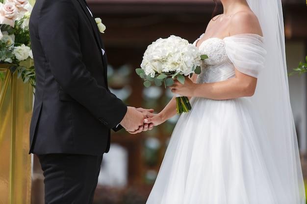 Braut im weißen kleid mit schönem strauß der weißen rosen und des bräutigams am hochzeitstag der hochzeit