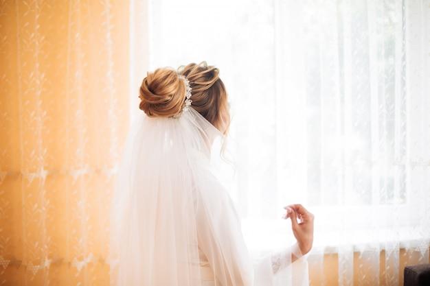 Braut im weißen kleid posiert während der vorbereitung auf die hochzeitszeremonie