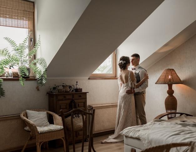 Braut im weißen kleid und bräutigam im anzug, posiert im weißen studio