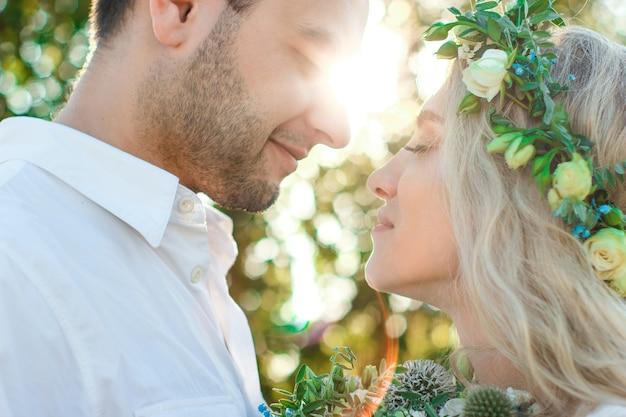 Braut im weißen kleid und kranz und bräutigamporträt am sonnigen sommertag rustikale hochzeit im freien