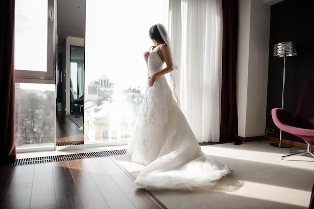 Braut im weißen spitzen- hochzeitskleid und im schleier, die durch das fenster schaut