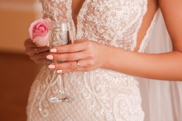 Braut im weißen spitzenkleid mit einem glas champagner und einer rose