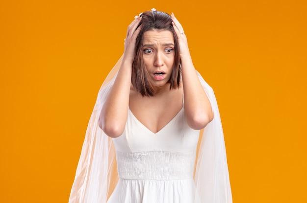 Braut im wunderschönen hochzeitskleid, die mit den händen auf dem kopf schockiert zur seite schaut