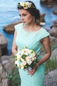 Braut in der natur in den bergen in der nähe des wassers. kleiderfarbe tiffany. braut posiert mit blumenstrauß.
