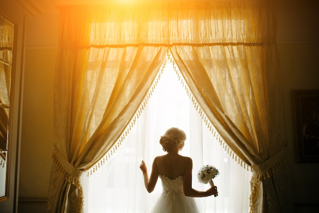 Braut in einem fenster mit blumenstrauß