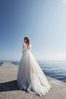 Braut in einem hochzeitskleid am strand am meer