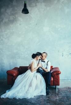 Braut in einem hochzeitskleid bräutigam in hosen und einem weißen hemd