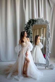 Braut in einem hochzeitskleid, das neben einem spiegel steht, der mit weihnachtsdekor verziert wird.