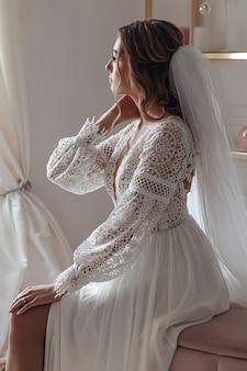 Braut in einem hochzeitskleid im boho-stil und mit einem schleier posierend in einem gemütlichen raum sitzend. hochzeitsfoto-session, brautmorgen.