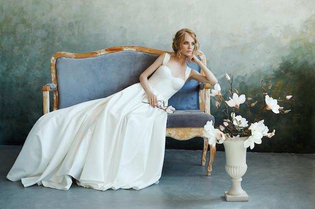 Braut in einem schicken langen kleid, das auf der sofacouch liegt. weißes hochzeitskleid