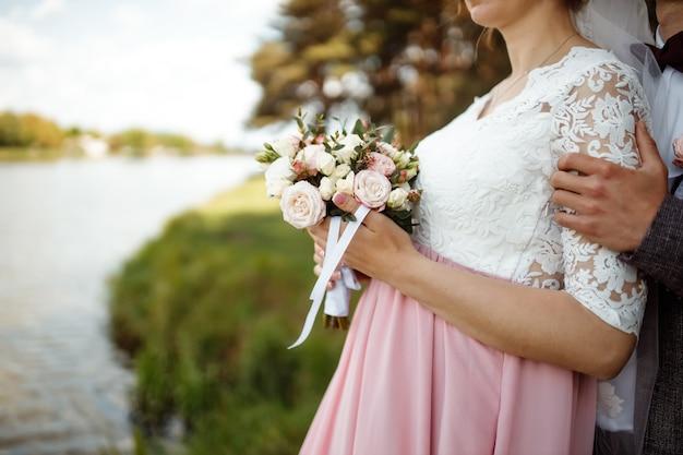 Braut in einem schönen kleid mit einem zug, der einen blumenstrauß und grün hält.