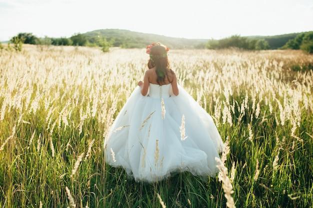 Braut in einem schönen langen kleid posiert im garten.