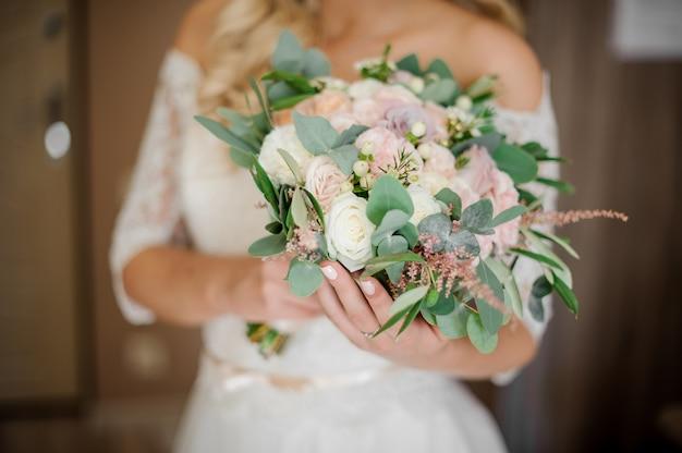 Braut in einem weißen kleid, das einen hochzeitsblumenstrauß hält
