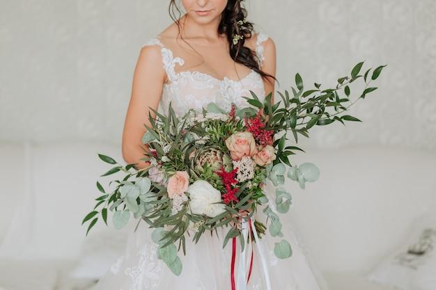 Braut in einem weißen kleid mit einem luxuriösen blumenstrauß mit eukalyptus verziert
