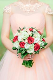 Braut in einem weißen kleid mit einem luxuriösen blumenstrauß verziert