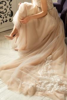 Braut in luxuriösem hochzeitskleid und schuhen auf high heels