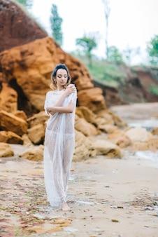Braut in unterwäsche und morgenmantel mit schleier geht am strand spazieren Premium Fotos