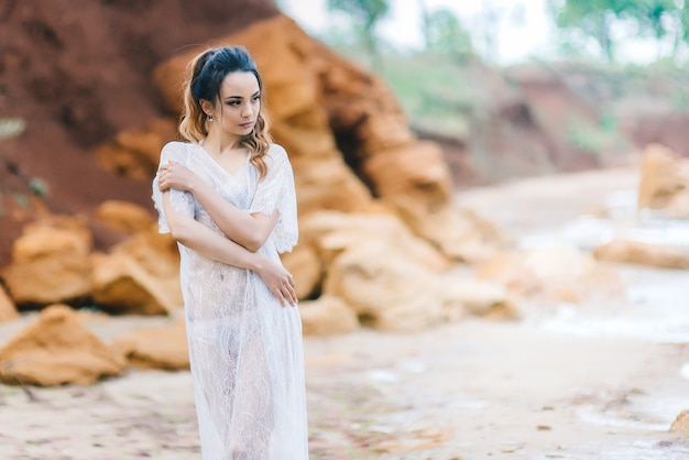Braut in unterwäsche und morgenmantel mit schleier geht am strand spazieren