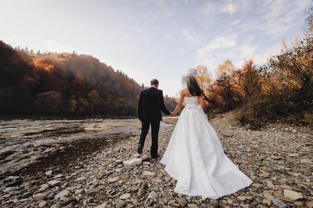 Braut in weißem kleid und bräutigam gehen zu den flussfelsen und händchen haltend