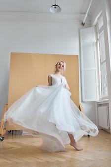 Braut ist eine frau in einem leichten sommerhochzeitskleid, die am fenster steht. blondes mädchen mit perfektem haar und schönem make-up