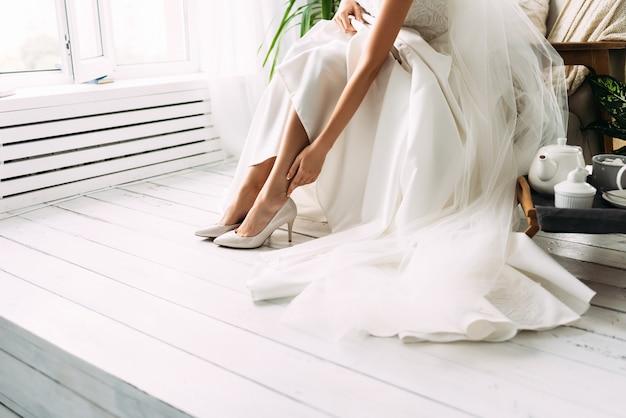 Braut kleidet schuhe vor der hochzeit