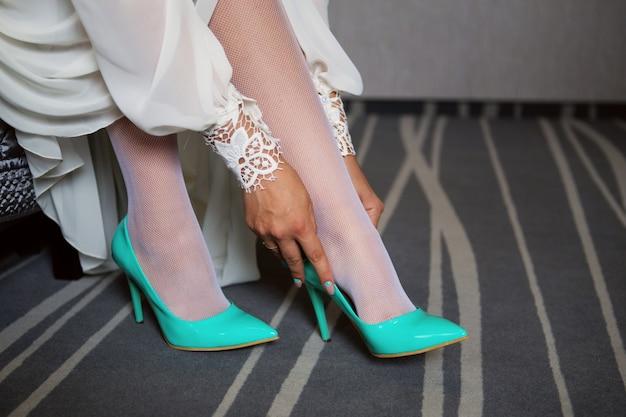 Braut kleidet schuhe vor der hochzeitszeremonie