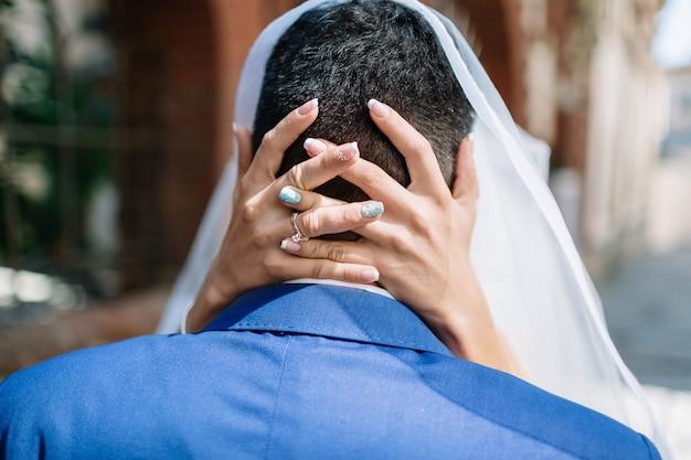 Braut kreuzt ihre hände auf den kopf des bräutigams