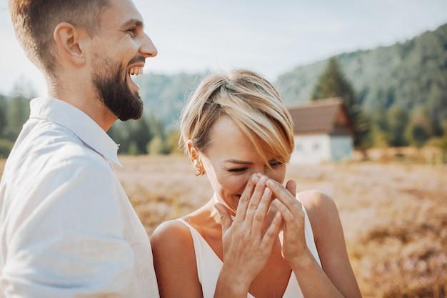Braut lacht, lehnend zu ihrem bräutigam, während sie auf dem feld darstellen