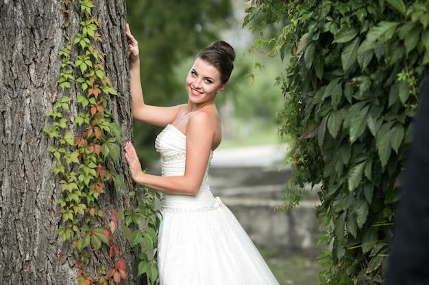 Braut lehnt an einem baum