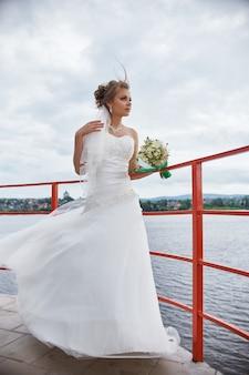 Braut mit blumen in ihren händen, die im wind stehen