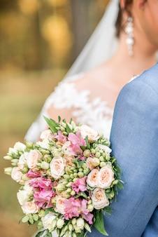 Braut mit blumenstrauß mit den weißen und rosa blumen