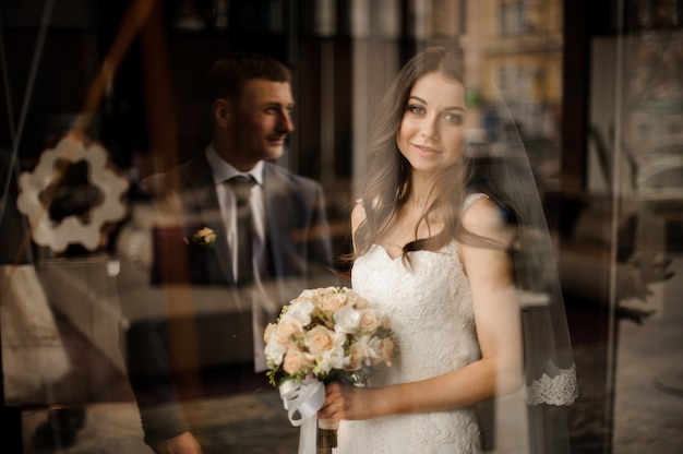 Braut mit blumenstrauß von rosen lächelnd und auf bräutigam wartend