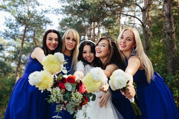 Braut mit brautjungfern hält sträuße posiert