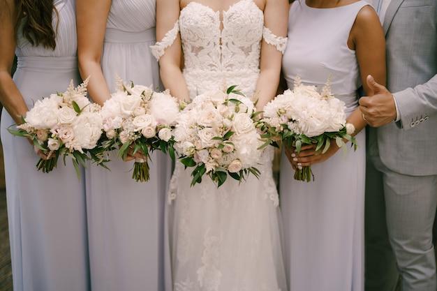 Braut mit brautjungfern mit blumensträußen stehen drinnen