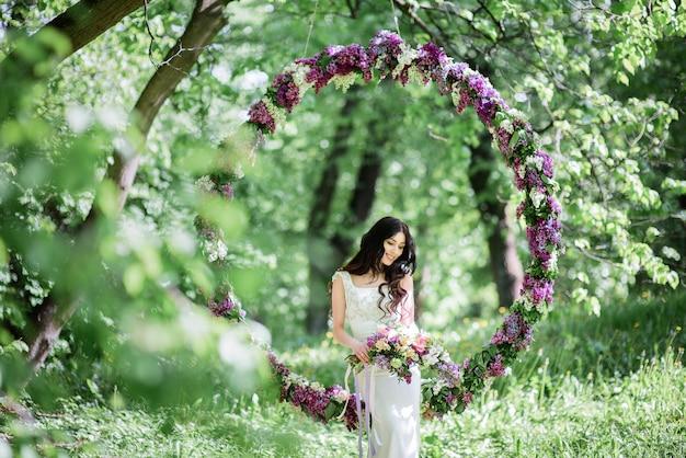 Braut mit dem langen dunklen haar sitzt auf einem großen kreis der flieder
