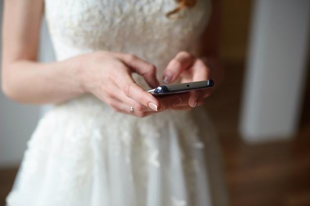 Braut mit dem telefon in ihren händen schreibt eine mitteilung.