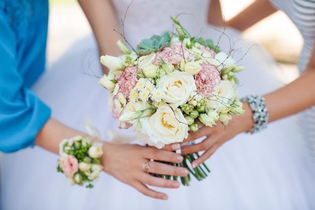 Braut mit den brautjungfern, die einen blumenstrauß halten.