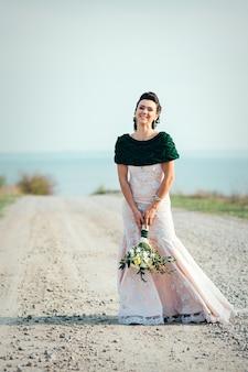 Braut mit einem blumenstrauß in einem elfenbeinfarbenen kleid und einem gestrickten schal auf der straße, die sich in die ferne erstreckt