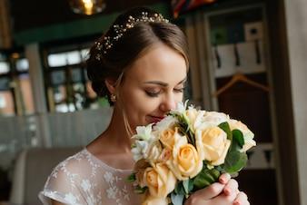 Braut mit einem Blumenstrauß, lächelnd. Hochzeitsporträt der schönen Braut. Hochzeit. Hochzeitstag.