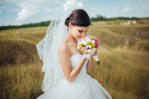 Braut mit einem blumenstrauß, lächelnd. hochzeitsporträt der schönen braut.