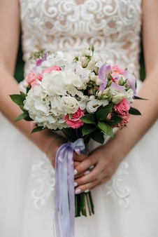 Braut mit einem schönen blumenstrauß in den händen, nahaufnahme