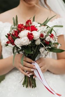 Braut mit einem schönen strauß roter rosen in den händen, nahaufnahme