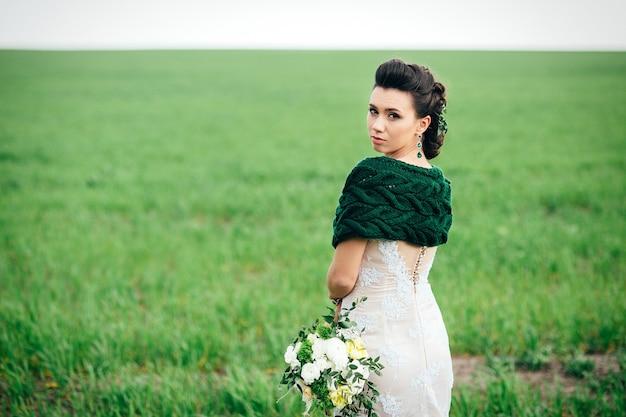 Braut mit einem strauß in einem elfenbeinfarbenen kleid und einem gestrickten schal auf einer grünen wiese