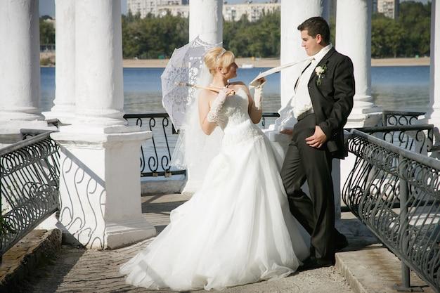 Braut mit einem weißen regenschirm und einem bräutigam stehen nahe dem fluss