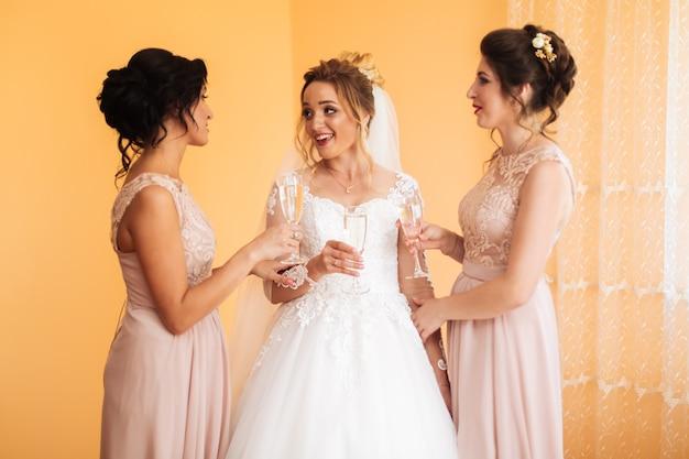 Braut mit fröhlichen freundinnen bei der hochzeit trinken champagner aus gläsern. braut und freundinnen umarmen sich im raum. morgen braut und freundinnen.