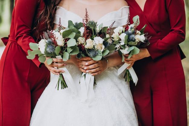 Braut mit hochzeitsblumenstrauß mitten in brautjungfern