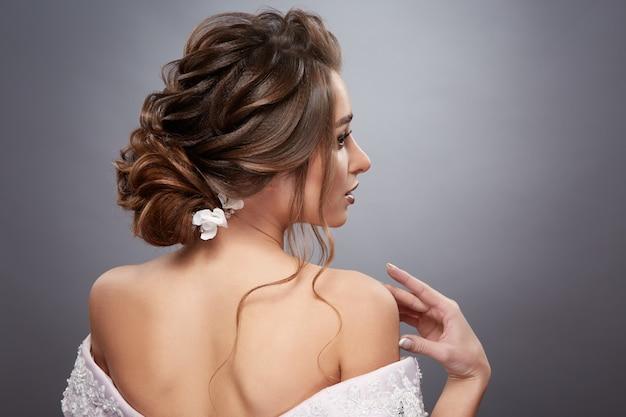 Braut mit hübscher frisur, die ihre schulter berührt und zur seite schaut